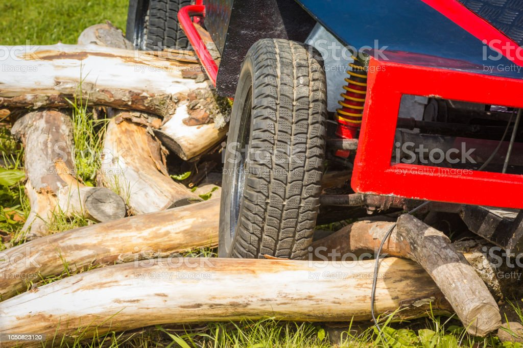 Red crawler wheels outside close-up. Rc car standing on wood stock photo