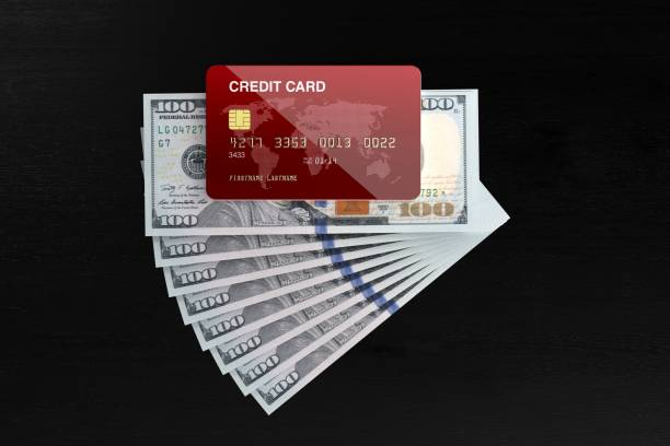 red credit card and one hundred american dollar bills on black background - money black background stock photos and pictures