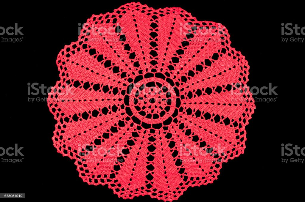 Red crocheted coaster on black background. Lace doily. stock photo