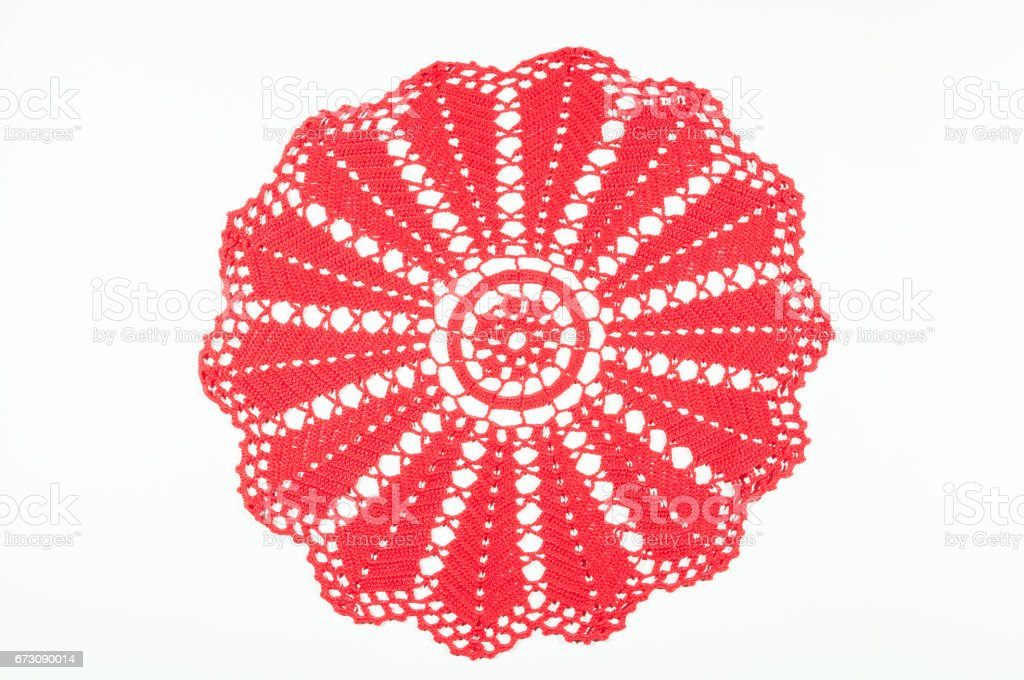 Red crocheted coaster on white background. Lace doily. stock photo
