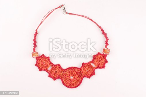 Red crocheted necklace isolated on white.