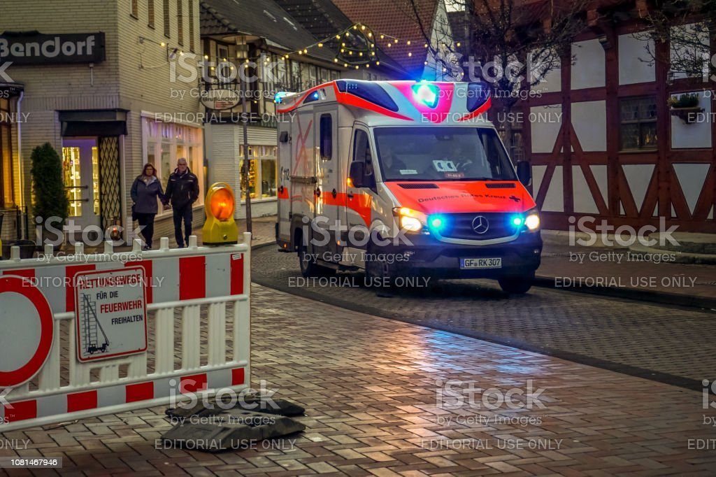 Red Cross ambulance drives through the old town in the early evening...