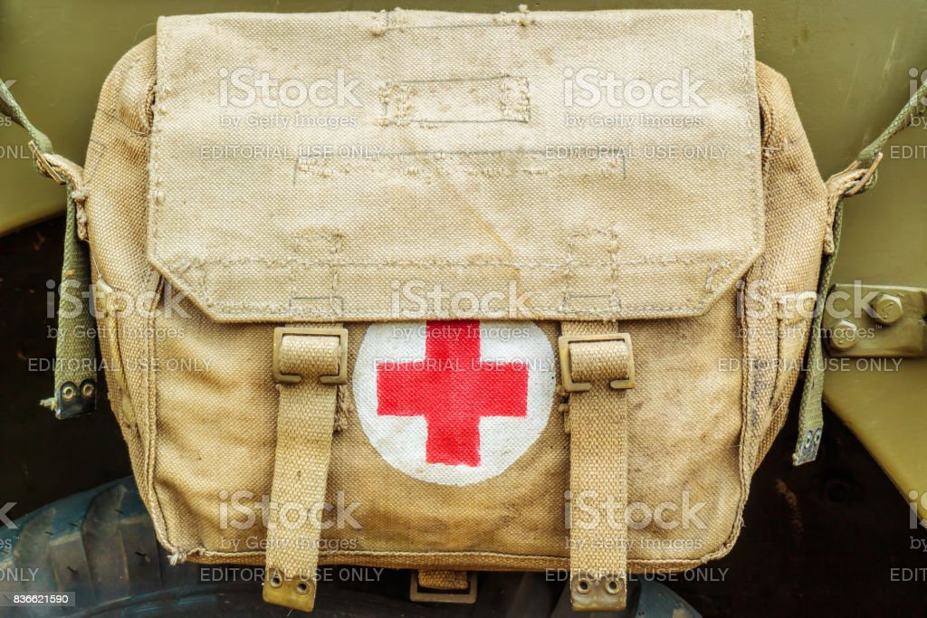 Red cross medical aid symbol on an old army bag stock photo