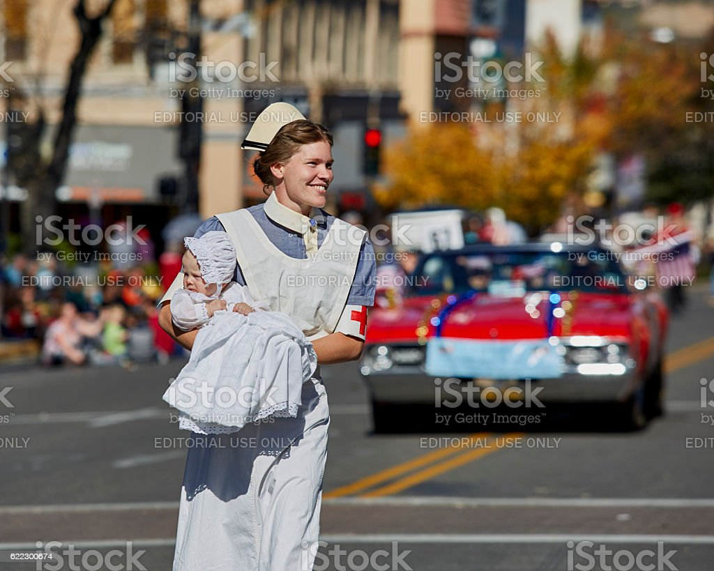Red Cross Nurse with Baby marching in Parade stock photo