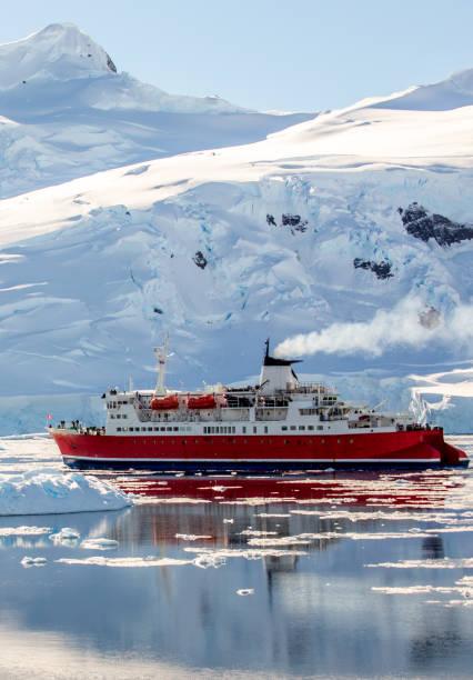 Rotes Kreuzfahrtschiff driftet zwischen den Eisbergen mit riesigem Fels und Gletscher im Hintergrund, Neco-Bucht, Antarktis – Foto