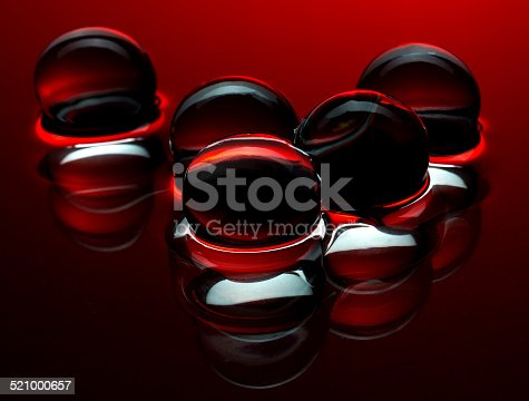 istock Red crystal balls in the water - abstract background 521000657
