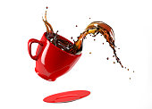 Red cup mug and saucer jumping with coffee splash. Isolated on white background. Clipping path included.