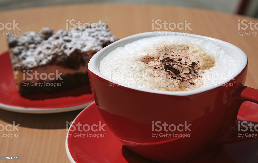 Red cup of cappuccino and chocolate cheese cake royalty-free stock photo