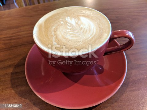 Red cup of Cappuccino on saucer with a leaf pattern in foam on table.