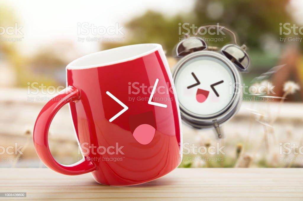 Rote Tasse Kaffee und Wecker mit einem glücklichen Lächeln auf Holztisch vor natürlichen Hintergrund in den Morgen. Guten Morgen und einen glücklichen Tag, guten Tag – Foto
