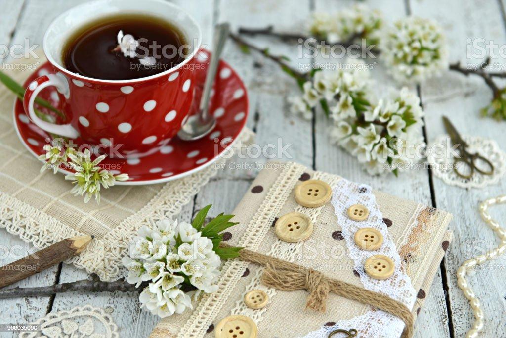 Rode kopje thee met hand gemaakt dagboek en pruimenboom takken in bloesem - Royalty-free Bloem - Plant Stockfoto