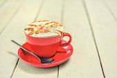 istock Red cup with coffee and cream with a spoon on 647611212