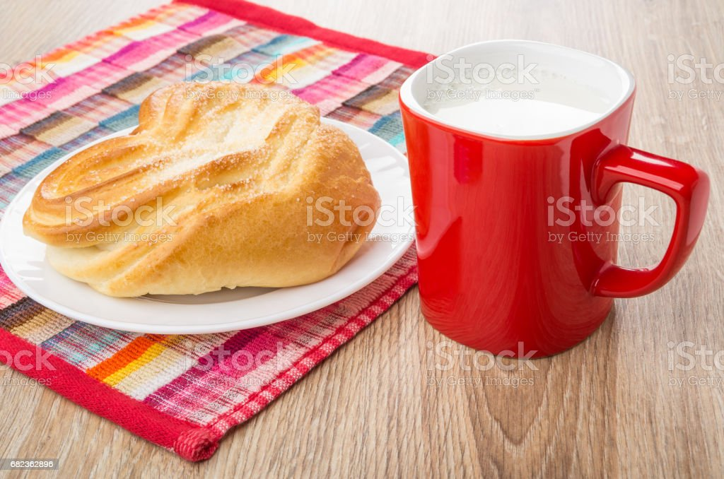 Red cup with milk, napkin and bun in white plate foto stock royalty-free