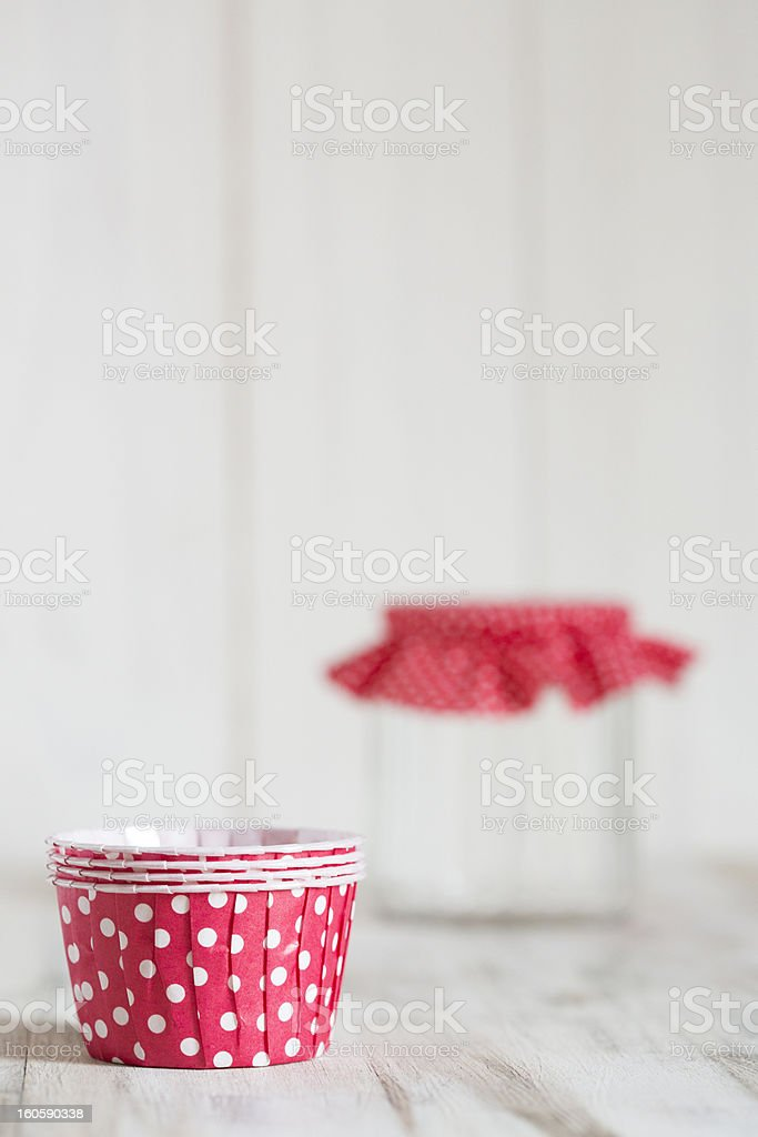 Red cupcake liners with a jar of polka dot fabric stock photo
