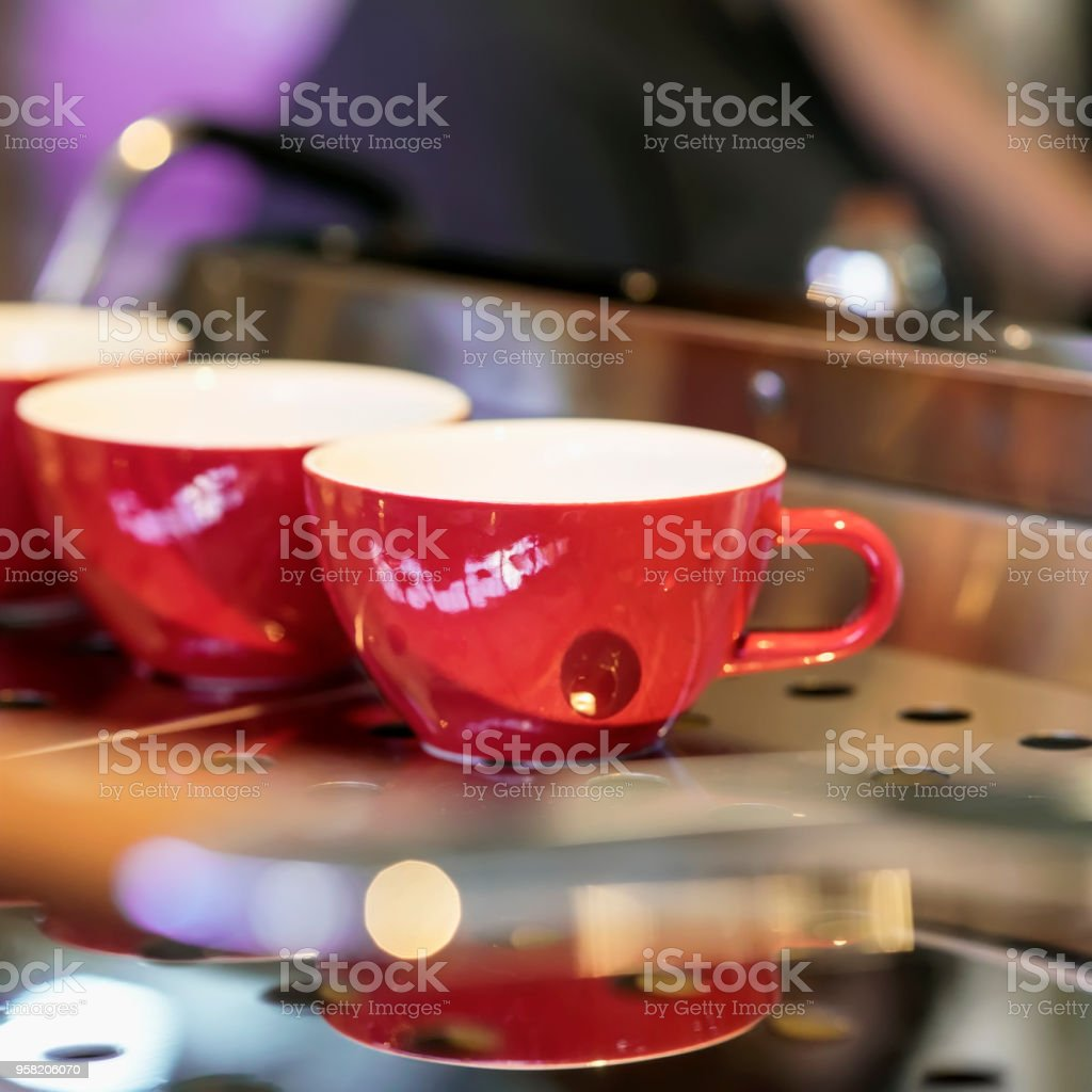 Red cups on the stand of the coffee machine, bar. Vintage dark tone,...
