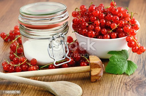 red currant jam making with sugar and fresh fruits. jar glass