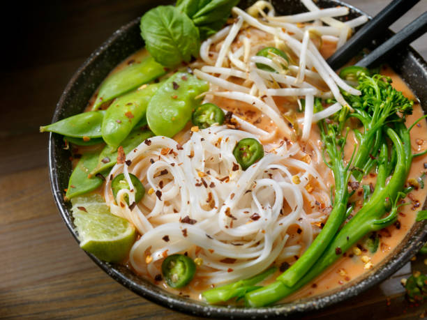 Red Curry Noodle Soup with Broccolini, Bean Sprouts and Fresh Basil, stock photo