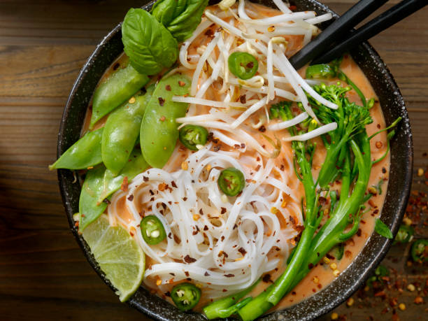 Red Curry Noodle Soup with Broccolini, Bean Sprouts and Fresh Basil, Thai Red Curry Noodle Soup with Broccoli, Bean Sprouts, Fresh Basil, Lime and Chili Flakes rice noodles stock pictures, royalty-free photos & images