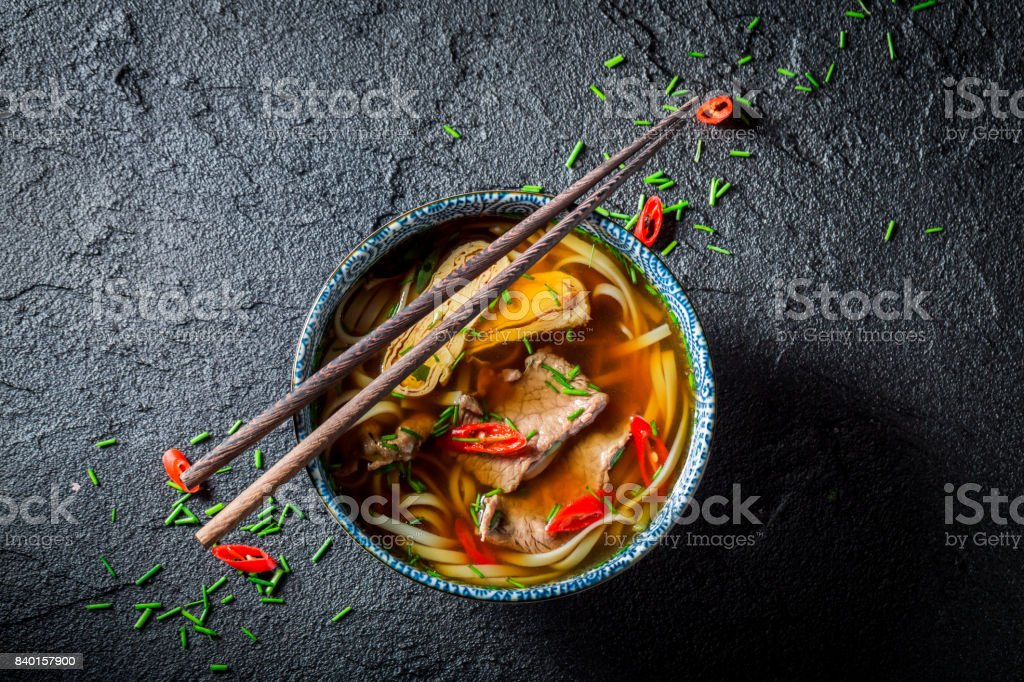 Red Curry soup with chopsticks on black table stock photo