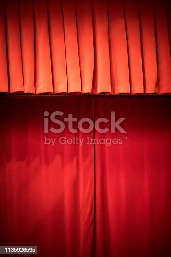 Image of a red curtain on a stage.
