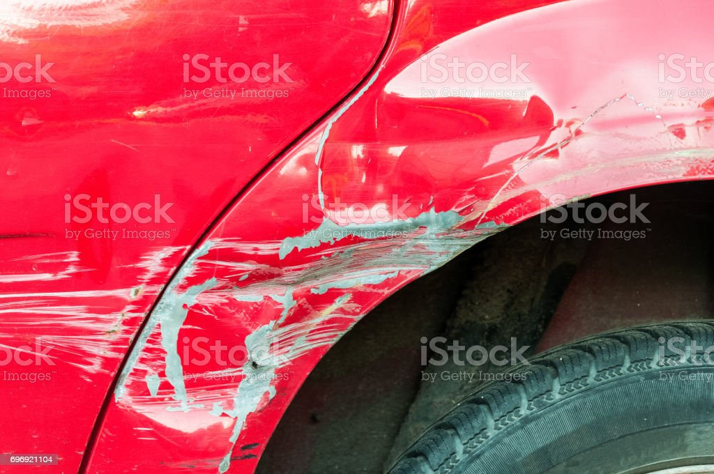 Red damaged car in car crash accident with scratched paint. stock photo