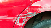 istock Red damaged car in crash accident with scratched paint and dented metal body 939044962