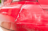 istock Red damaged car in crash accident with scratched paint and dented rear bumper metal body 960762206