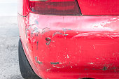 istock Red damaged car in crash accident with scratched paint and dented rear bumper metal body 974817304