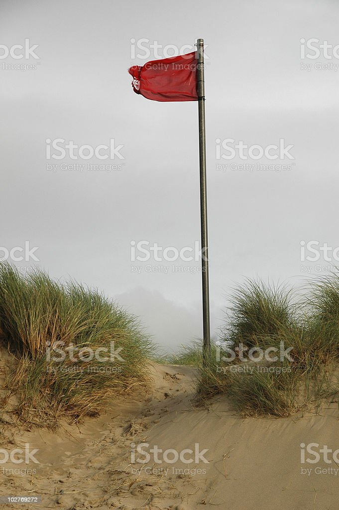 Red danger flag on a beach stock photo