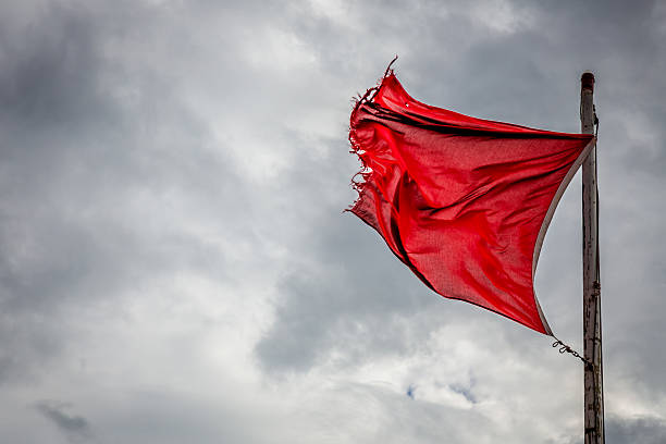 Red Danger Flag A wind torn red warning flag indicating danger on an English beach. red cloth stock pictures, royalty-free photos & images