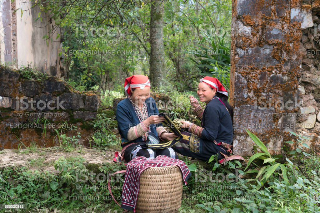 Red Dao ethnic minority women embroider their traditional brocade products beside the ancient wall stock photo