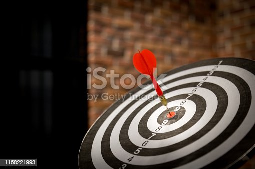 Red dart arrow hitting in the target center of dartboard on bullseye with sun light vintage style, Target marketing and business success concept