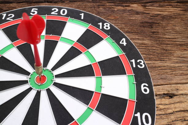 red dart arrow hitting in the target center of dartboard - target australia stock pictures, royalty-free photos & images
