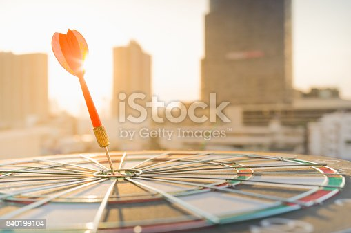 istock Red dart arrow hitting in the target center of dartboard with modern city and sunset background. Target business, achieve and victory concept . 840199104