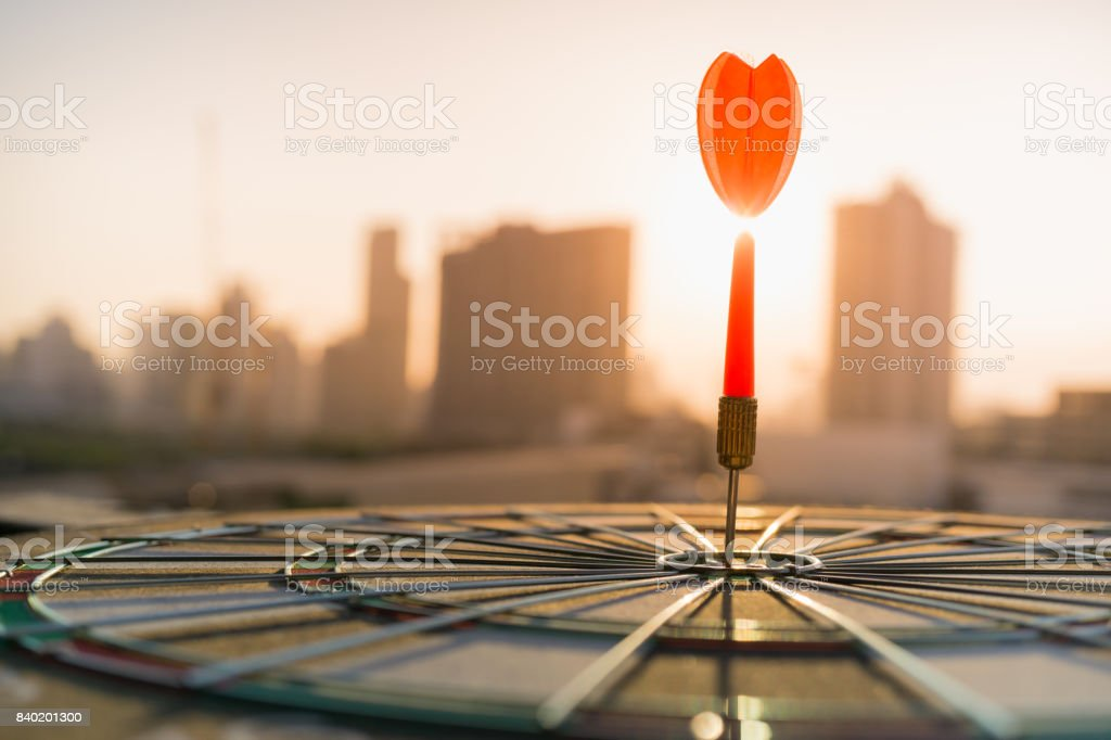 Red dart arrow hitting in the target center of dartboard with modern city and sunset background. Target business, achieve and victory concept . Red dart arrow hitting in the target center of dartboard with modern city and sunset background. Target business, achieve and victory concept . Accuracy Stock Photo