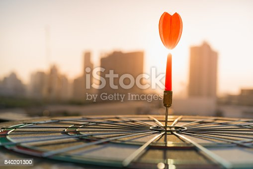 istock Red dart arrow hitting in the target center of dartboard with modern city and sunset background. Target business, achieve and victory concept . 840201300