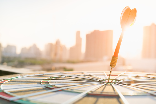 istock Red dart arrow hitting in the target center of dartboard with modern city and sunset background. Target business, achieve and victory concept . 840201636