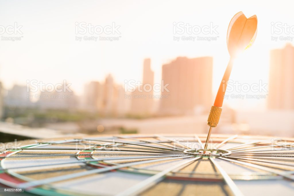 Red dart arrow hitting in the target center of dartboard with modern city and sunset background. Target business, achieve and victory concept . stock photo