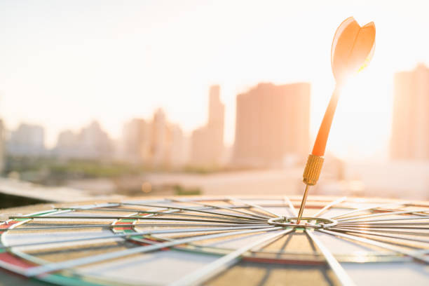 Red dart arrow hitting in the target center of dartboard with modern city and sunset background. Target business, achieve and victory concept . - foto stock