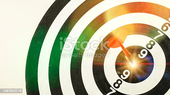 istock Red dart arrow hitting in the target center of dartboard with Shining light. 1087842218