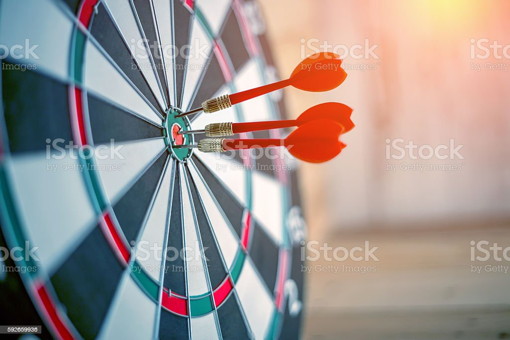 Red dart arrow hitting in the target center stock photo