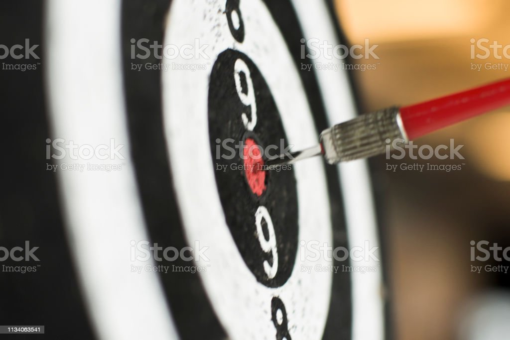 Dart board hanging with red dart hit on target on blurry background