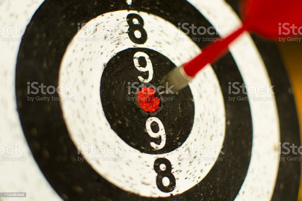 Dart board hanging with red dart hit on target.