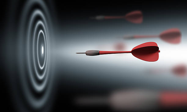 A red dart shooting toward a black and white bullseye stock photo