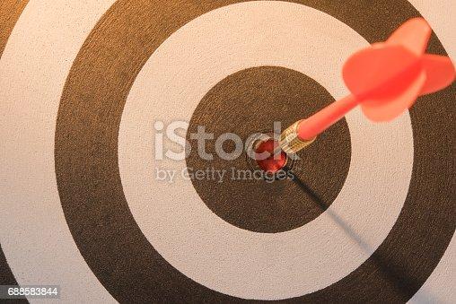 istock Red dart target arrow hitting on bullseye with sun light 688583844