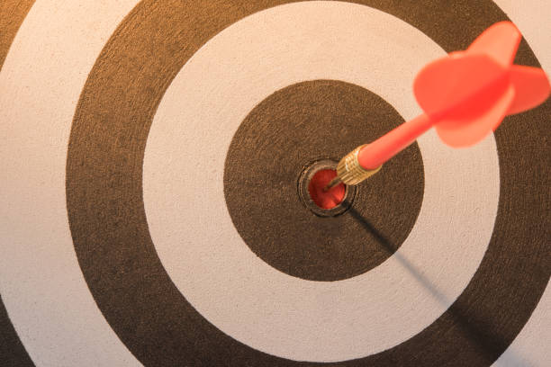 Red dart target arrow hitting on bullseye with sun light stock photo