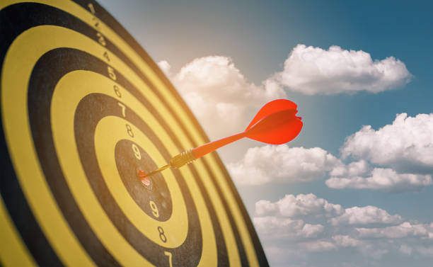 Red darts arrows in the center of dartboard with blue sky background, in the business goal concept