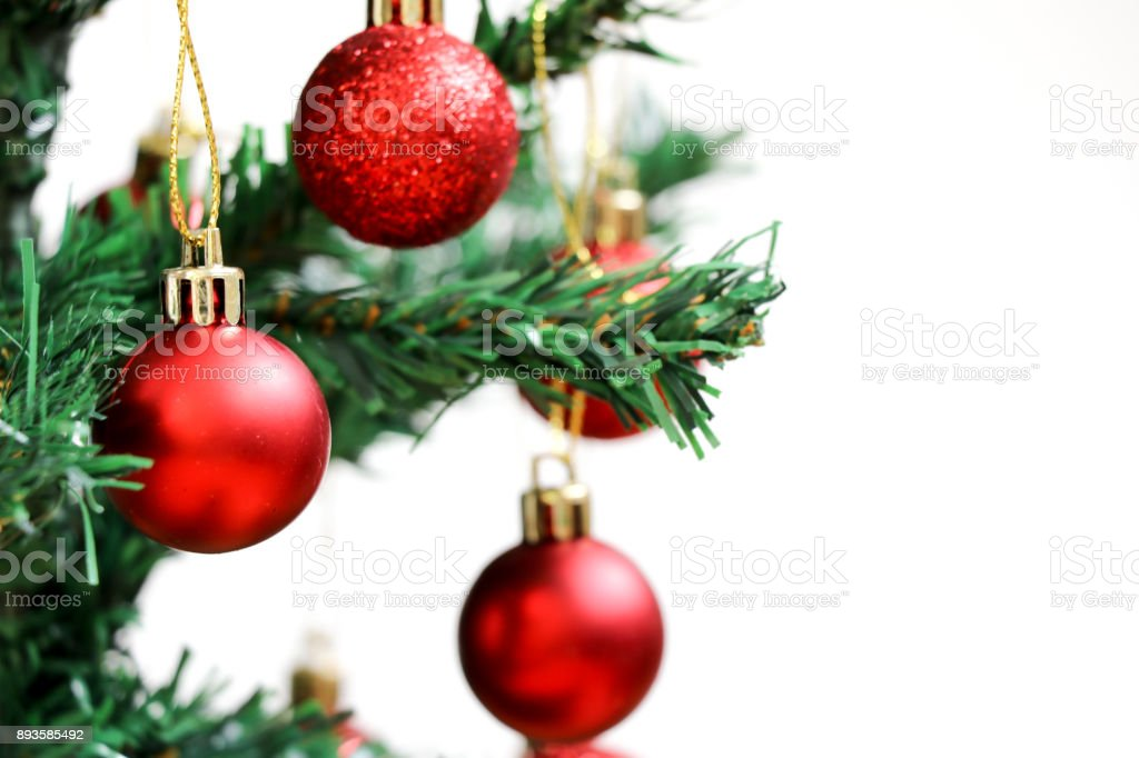 Red decoration ball on green christmas tree with white background stock photo