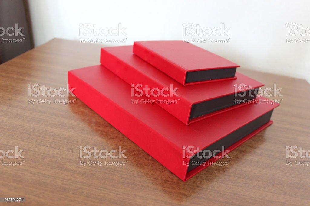 Three decorative protective carton book boxes on wooden table in...
