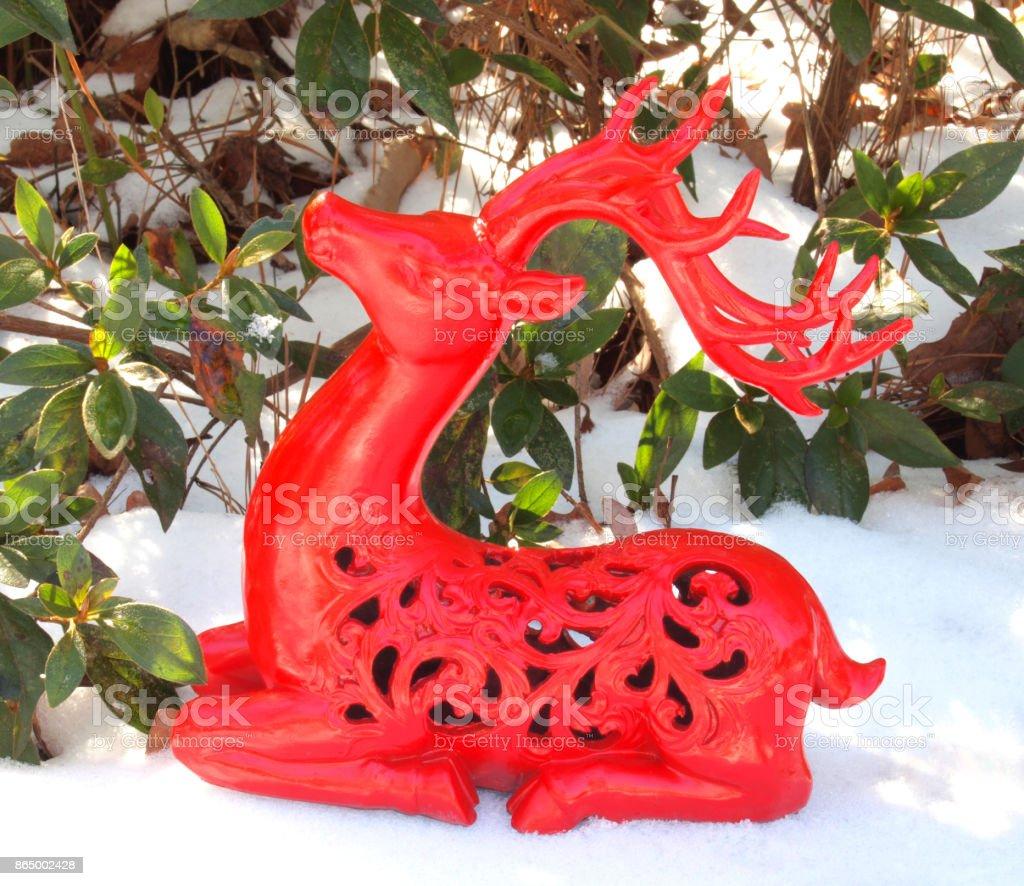 Red Deer Figurine Sitting in Snow stock photo